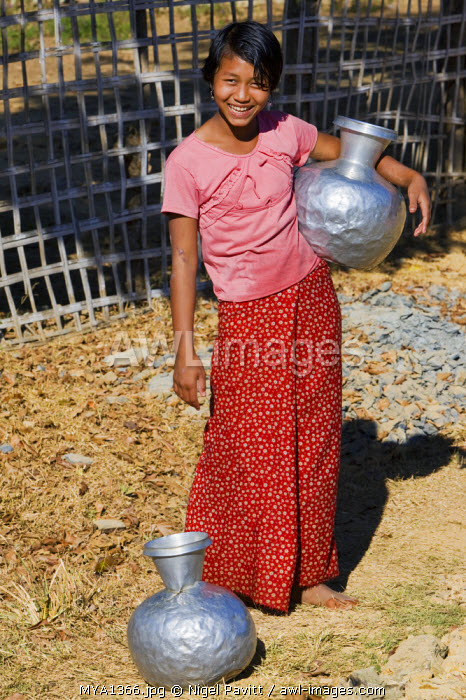 Myanmar, Burma, Mrauk U. A Rakhine girl with aluminium water containers at Mrauk U.  These containers are imported from India or Bangladesh.