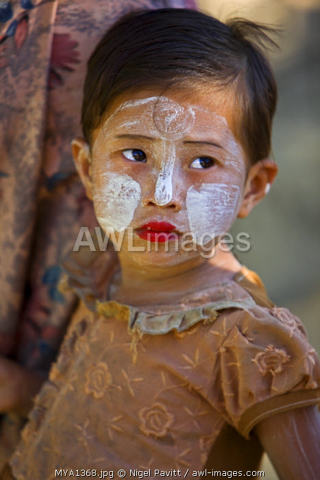 Myanmar, Burma, Mrauk U. A young That girl at Mrauk U with her face decorated with Thanakha, a popular local sun cream and skin lotion.