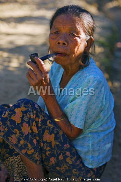 Myanmar, Burma, Mrauk U. An old That woman smoking a pipe at Mrauk U.  That women traditionally pierce and extend their earlobes to insert metal hoops.