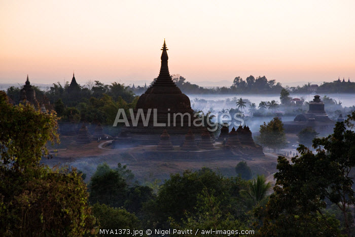 Myanmar, Burma, Mrauk U. Smoke swirls around the historic bell-shaped temples of Mrauk U at dusk. They were built in the Rakhine style between the 15th and 17th centuries.