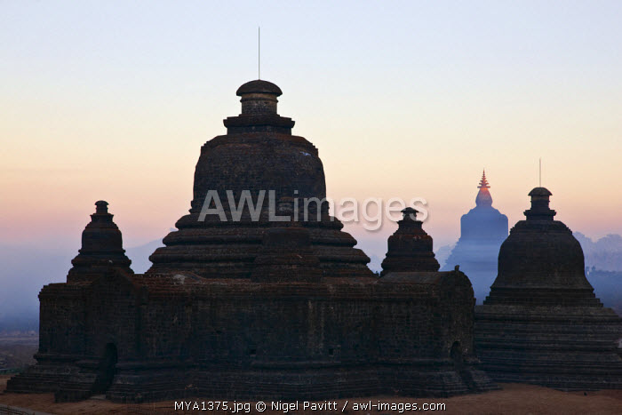Myanmar, Burma, Mrauk U. Early morning mist swirls around the historic bell-shaped temples of Mrauk U which were built in the Rakhine style between the 15th and 17th centuries.