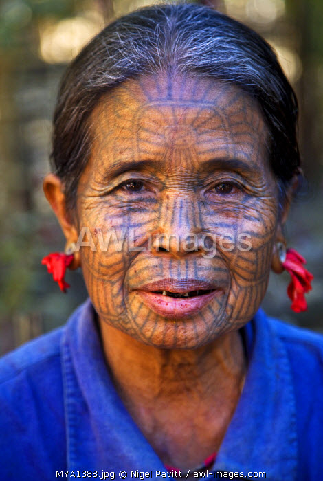 Myanmar, Chin State, Kyi Chaung Village. A Chin woman with tattooed face and mouth stained red due to her habit of chewing beetle nut. Girls used to be tattooed at the age of 14 or 15 years.