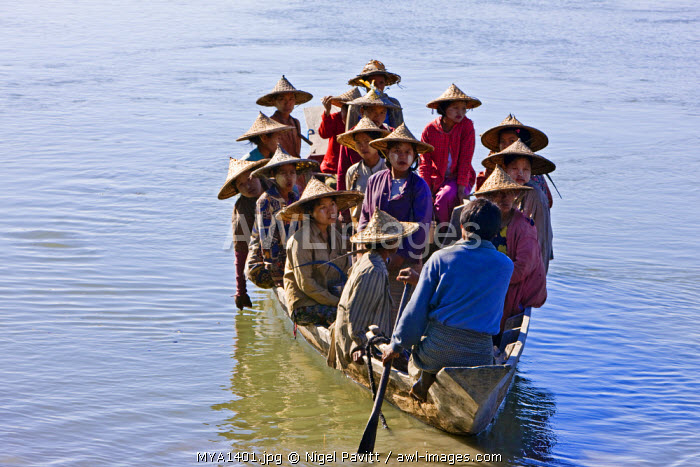 Myanmar, Burma, Rakhine State, Gyi Dawma. In the early morning, the women of Gyi Dawma village cross the Kaladan River by boat to tend their fields on the far side.