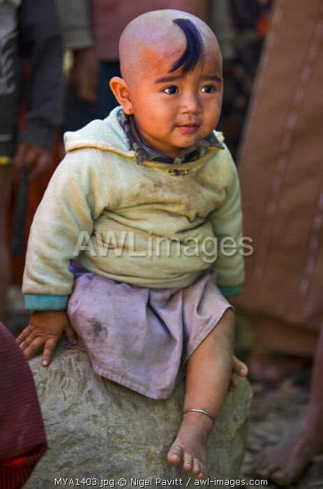 Myanmar, Burma, Rakhine State, Gyi Dawma. A young girl at Gyi Dawma village. The small tuft of hair on her shaven head is believed to protect her.