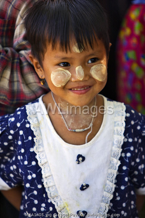 Myanmar, Burma, Rakhine State, Gyi Dawma. A young girl at Gyi Dawma village with her face decorated with Thanakha, a local sun cream and skin lotion.