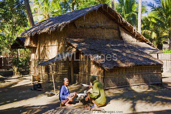 Myanmar, Burma, Rakhine State, Gyi Dawma. A bamboo house at Gyi Dawma village with the owners, an old couple, taking their morning meal outside.