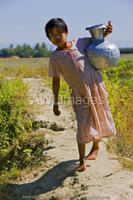 awl-images.com - Myanmar / Myanmar, Burma, Rakhine State, Laung Shein. A young girl from Laung Shein village collects water from a nearby dam. Her face is decorated with Thanakha, a local sun cream and skin lotion.