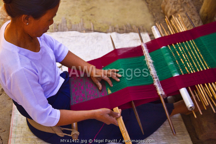 Myanmar, Burma, Rakhine State, Laung Shein. A woman at Laung Shein village weaves brightly coloured cloth at a loom beside her house. Almost every family at Laung Shein has a loom.