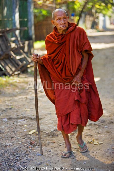Myanmar, Burma, Rakhine State, Sittwe. An old Buddhist monk walking down a street of Sittwe.