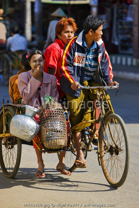 Myanmar, Burma, Rakhine State, Sittwe. A bicycle taxi, known as a trishaw, is an inexpensive means of transport throughout Myanmar. Passengers sit back to back in the sidecar.