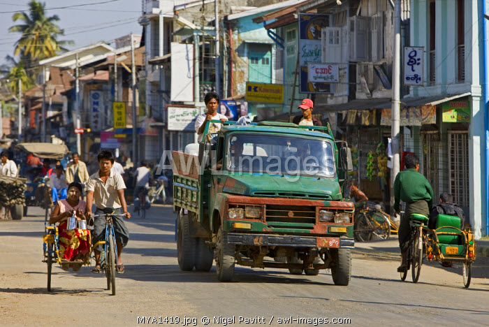 Myanmar, Burma, Rakhine State, Sittwe. A busy street scene in Sittwe.  Bicycle taxis, known as a trishaws, are an inexpensive and popular means of transport throughout Myanmar.
