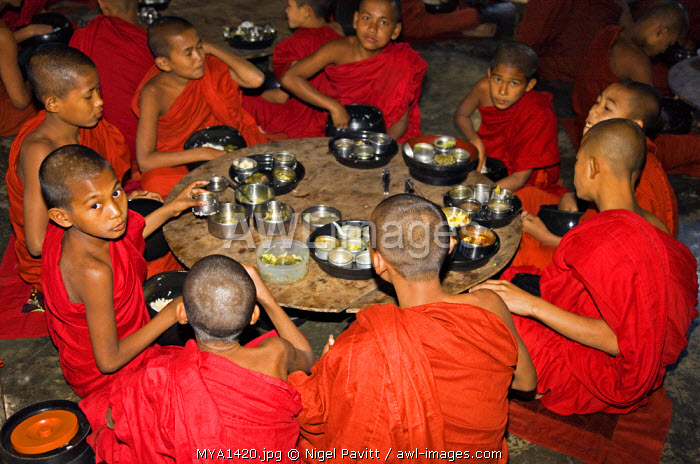 Myanmar, Burma, Rakhine State, Sittwe. Young novice monks eat their main meal at Pathain Monastery where 210 monks live. All their food is donated daily by the community.