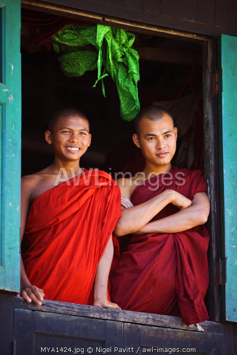 Myanmar, Burma, Rakhine State, Sittwe. Two novice monks look out of their dormitory window at the Pathain Monastery. Most early learning takes place in monastery schools.