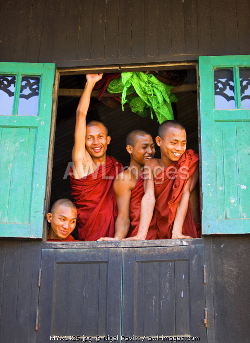 Myanmar, Burma, Rakhine State, Sittwe. Cheerful novice monks look out of their dormitory window at the Pathain Monastery. Most early learning takes place in monastery schools.