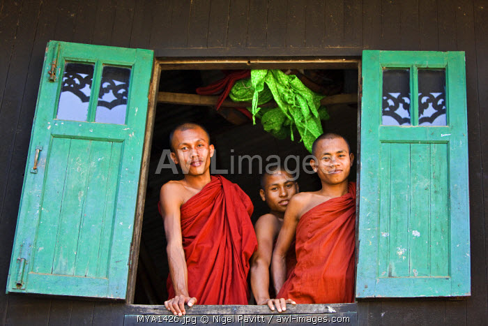 Myanmar, Burma, Rakhine State, Sittwe. Three novice monks look out of their dormitory window at the Pathain Monastery. Most early learning takes place in monastery schools.