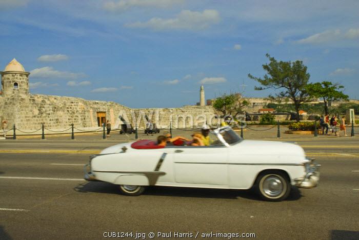 Cuba, Havana. Classic vintage American car driving on the Malecon, Havana
