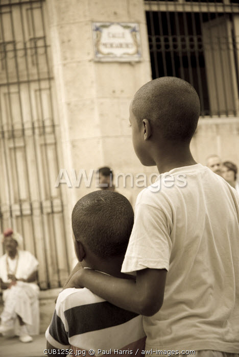 Cuba, Havana. Boys watching impromtu street parade, Plaza Vieja