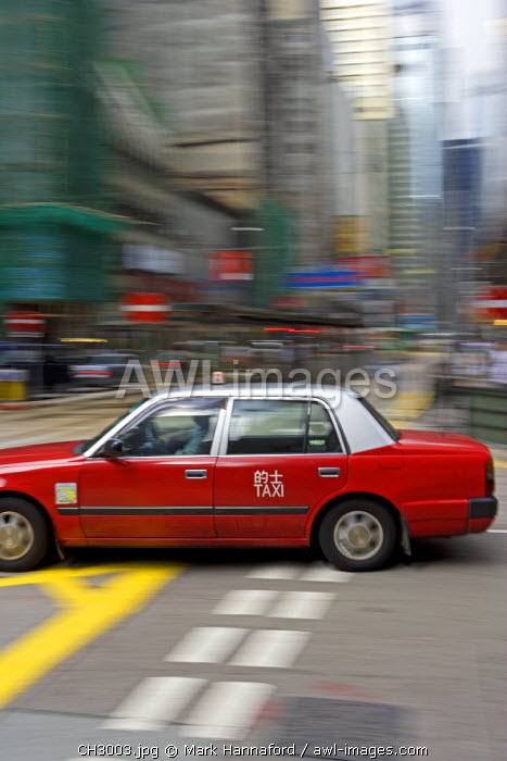 China, Hong Kong. A city taxi moves at speed through the busy downtown area of Hoong Kong island rushing to pick up a passenger.