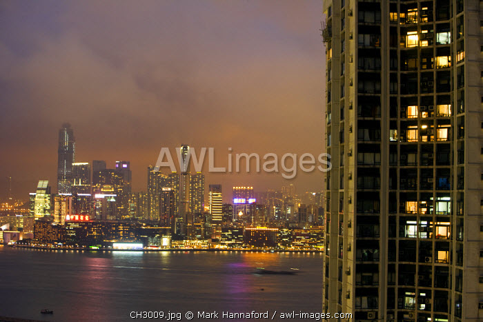 China, Hong Kong, Causeway Bay.  Looking across at the illuminated Kowloon skyline from Hong Kong Island with a Star Ferry blurring the foreground.