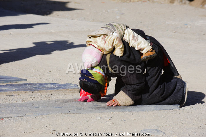awl-images.com - China / China, Gansu Province, Xiahe, Labrang Monastery, pilgrim praying on the road