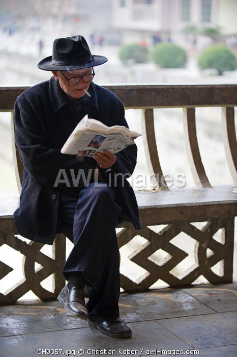 awl-images.com - China / China, Guizhou Province, Taijiang, old man reading a newspaper
