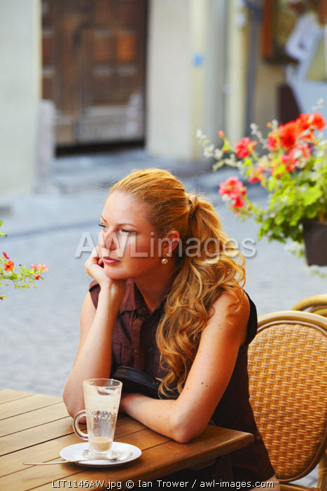 Lithuania, Vilnius, Woman Drinking Coffee At Cafe On Pilies Gatve (MR)