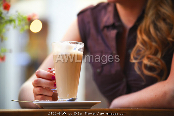 Lithuania, Vilnius, Woman Sitting At Cafe Drinking Coffee (MR)