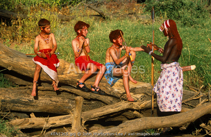 Kenya, Samburu National Reserve.  Children on a family safari learn local ways from a Samburu warrior.