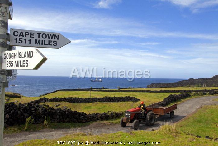 Tristan Da Cunha Island, settlement capital of Edinburgh, a farm tractor drives along one of the few island roads as a supply frieghter from Cape Town lies offshore