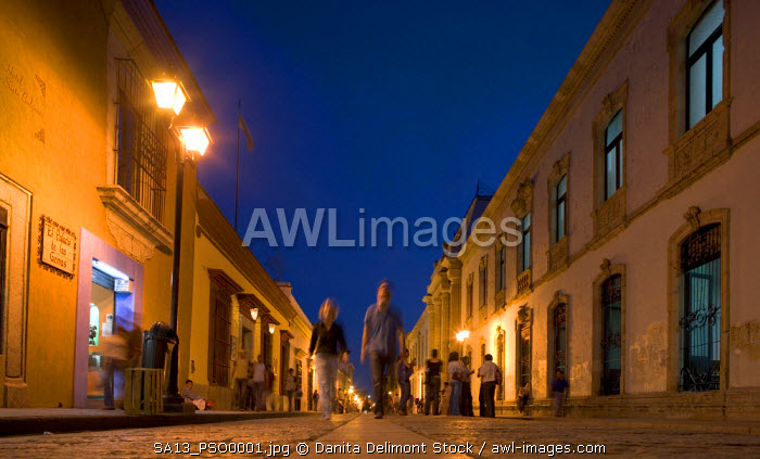 Mexico, Oaxaca, Window shoppers walk along cobblestone pedestrian street past galleries and shops near the Zocola in city's historic center at dusk