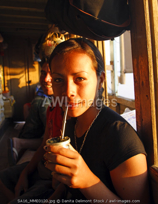 Young woman drinking terere': cold inusion of water and Ilex paraguayensis leaves.