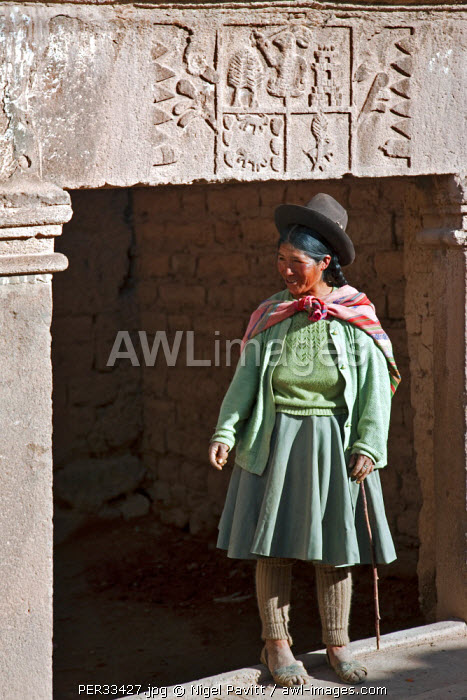 Peru, An Indian woman stands at the entrance to her house with a Spanish nobility coat of arms, an indication of the past.