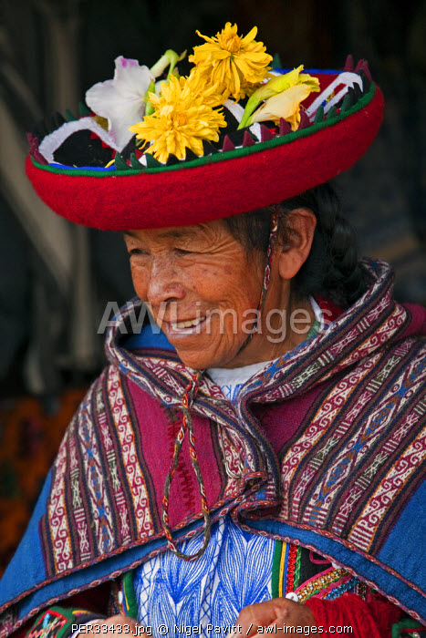 Peru, An old woman in traditional Indian costume with her round, saucer-shaped hat decorated with fresh flowers.