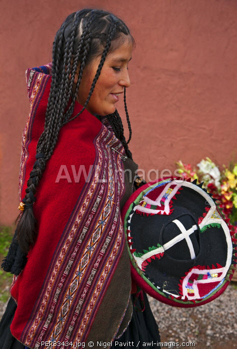 Peru, A young woman in traditional Indian costume with long braided hair.