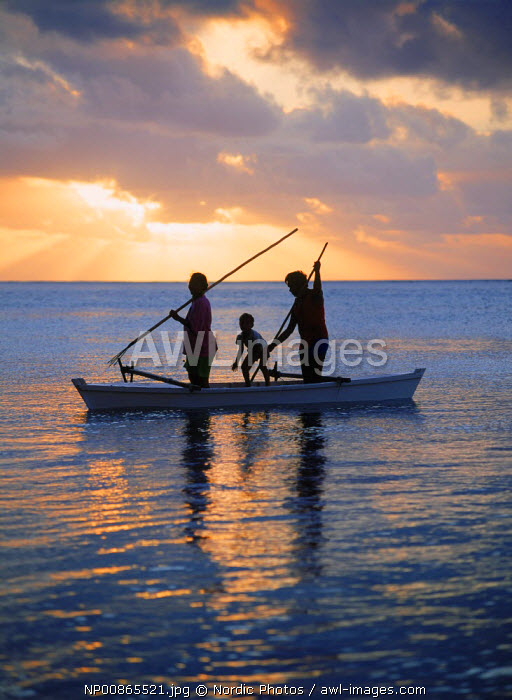 Family in outrigger canoe spearfishing on Aitutaki lagoon at sunset, Cook Islands