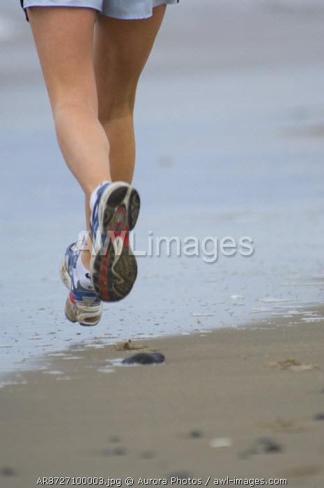 A woman running the north central Oregon Coast, Oregon. USA