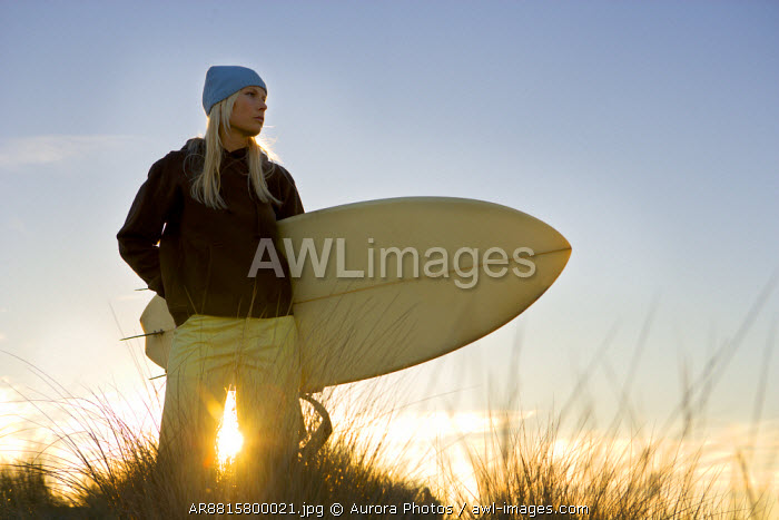 awl-images.com - USA / A woman stands with her surfboard at sunrise and checks out the morning waves at Ocean Beach in San Francisco, California. USA