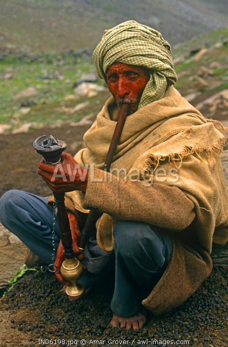 India, Himachal Pradesh, Chamba Valley. A Gaddi (semi-nomadic shepherd) from Chamba smokes a hookah, or water pipe, on the trail linking Kugti village, Kugti Pass and the summer grazing meadows of Lahaul.