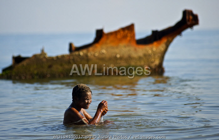 A woman bathes in the ocean in front of the rusted wreckage of a ship during a voodoo festival in Haiti.