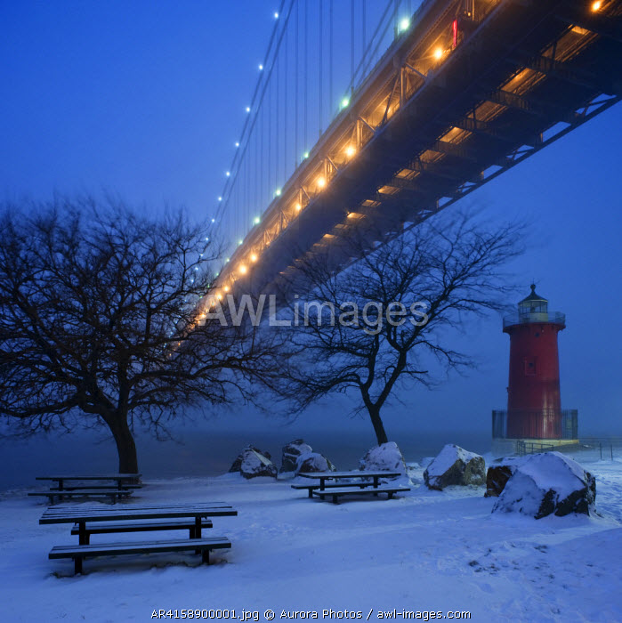 awl-images.com - USA / A little red lighthouse sits beneath a large bridge in the snow at dusk