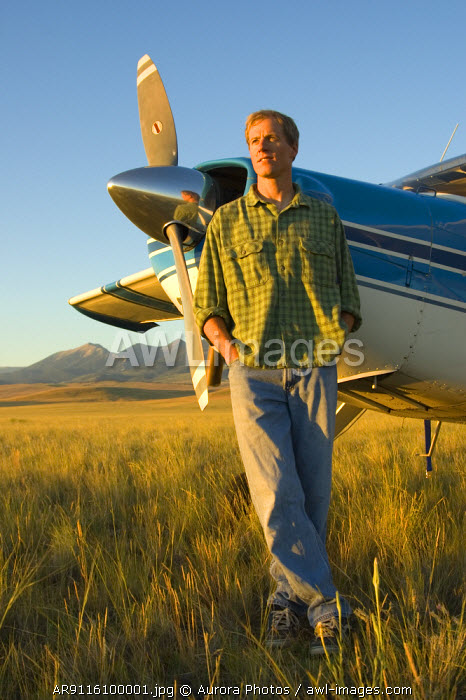 awl-images.com - USA / A man stands in a field next to his airplane with mountains in the background near Bozeman, Montana