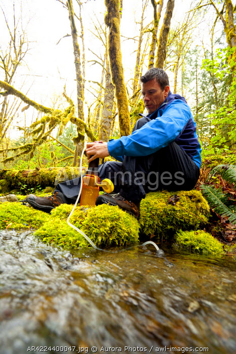 awl-images.com - USA / A young woman filtering water on a river in the rainforest, Mt Baker-Snoqualmie National Forest, Washington