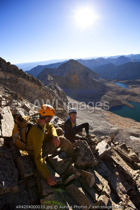 awl-images.com - USA / Two young men sit on a exposed ridge line taking a break while mountain climbing
