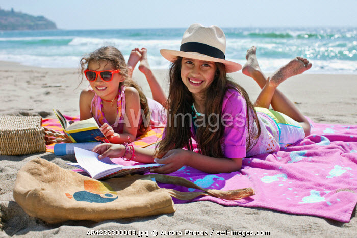 awl-images.com - USA / Two young girls reading on the sand in Torrance Beach in Los Angeles, California, USA