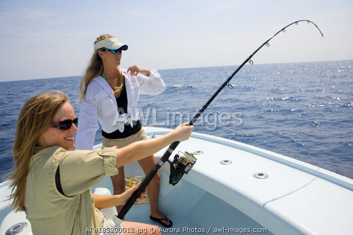 awl-images.com - USA / Two women are fishing on the bow of a boat with the rod bending on a catch