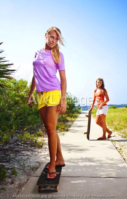 awl-images.com - USA / A girl skateboards while her friend watches on a sidewalk connecting the Santa Rosa Sound with the Gulf of Mexico, Florida, USA