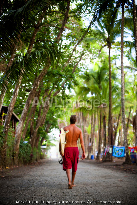awl-images.com - Costa Rica / A man wearing red shorts walks down a dirt road carrying a surfboard, Costa Rica