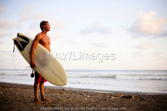awl-images.com - Costa Rica / A man stands on the beach with his surfboard looking out to the ocean, Costa Rica