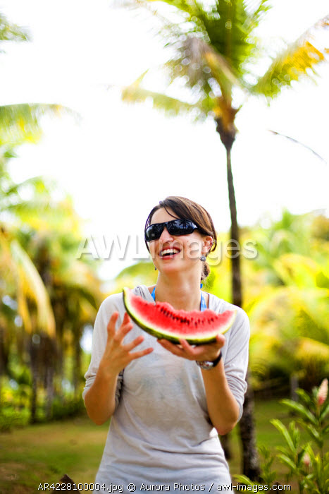 awl-images.com - Costa Rica / A woman smiles while eating a piece of watermelon, Costa Rica