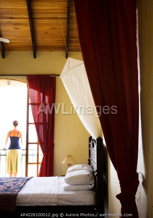awl-images.com - Costa Rica / A woman stands on a balcony outside her bedroom, Costa Rica